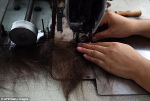 A worker feeds hair through a sewing machine during the production phase before it is sold